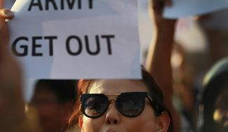 "An anti-coup protester holds a banner and shouts during a demonstration at the Victory Monumet in Bangkok, Thailand Saturday, May 24, 2014. Thailand's coup leaders said Saturday that they would keep former Prime Minister Yingluck Shinawatra, Cabinet members and anti-government protest leaders detained for up to a week to give them ""time to think"" and to keep the country calm. They also summoned outspoken academics to report to the junta. (AP Photo/Wason Wanichakorn)"
