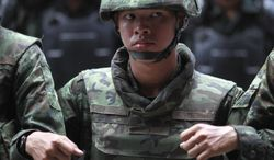 """Thai soldiers link arms as they monitor the protest against the coup outside a shopping complex in Bangkok, Thailand Saturday, May 24, 2014. Thailand's coup leaders said Saturday they will keep former Prime Minister Yingluck Shinawatra, Cabinet members and anti-government protest leaders detained for up to a week to give them """"time to think"""" and to keep the country calm. They also summoned outspoken academics to report to the junta. (AP Photo/Wason Wanichakorn)"""