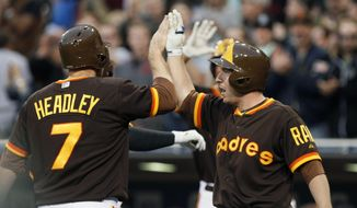 San Diego Padres' Chase Headley, left, high fives with teammate Jedd Gyorko after scoring on a two-run home run by Yonder Alonso in the first inning of a baseball game against the Chicago Cubs, Friday, May 23, 2014, in San Diego. (AP Photo/Don Boomer)