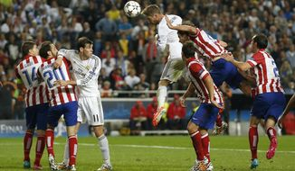 Real Madrid's Sergio Ramos, center, scores his side's first goal during the Champions League final soccer match against Atletico Madrid at the Luz Stadium in Lisbon, Portugal, Saturday, May 24, 2014. (AP Photo/Andres Kudacki)