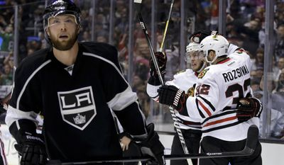 Chicago Blackhawks center Jonathan Toews, center, celebrates his goal with teammate Michal Rozsival, right, as Los Angeles Kings defenseman Jake Muzzin skates off during the first period of Game 3 of the Western Conference finals of the NHL hockey Stanley Cup playoffs in Los Angeles, Saturday, May 24, 2014. (AP Photo/Chris Carlson)