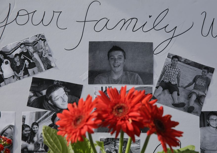 Images of Christopher Martinez are displayed as part of a memorial in front of the IV Deli Mart, where part of Friday night's mass shooting took place, on Sunday, May 25, 2014, in the Isla Vista beach community of Santa Barbara, Calif. Sheriff's officials said Elliot Rodger, 22, went on a rampage near the University of California, Santa Barbara, stabbing three people to death at his apartment before shooting and killing three more in a crime spree through a nearby neighborhood. (AP Photo/Chris Carlson)