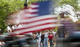 Marine veteran, retired Staff Sgt. Tim Chambers salutes riders in the annual Rolling Thunder 'Ride for Freedom' motorcycle rally in Washington, Sunday, May 25, 2014. (AP Photo/Molly Riley)