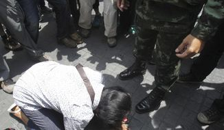 An anti-coup protester cries as she asks a Thai soldier to go away during a demonstration in Bangkok, Thailand, Sunday, May 25, 2014. The top general in Thailand's ruling junta warned people Sunday not to join anti-coup street protests, saying normal democratic principles cannot be applied at the time, as troops fanned out in central Bangkok to prevent rallies.(AP Photo/Sakchai Lalit)