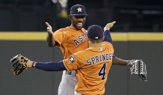 Houston Astros' Dexter Fowler, left, and George Springer (4) share congratulations after the team beat the Seattle Mariners in a baseball game Sunday, May 25, 2014, in Seattle. The Astros won 4-1. (AP Photo/Elaine Thompson)