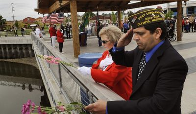 Post Commander Bill Doucette is joined by post Auxiliary member Georgia Watson as they toss flowers into Budd Inlet in remembrance of veterans who lost their lives at sea while serving their country near the conclusion of the annual Memorial Day Waterside Ceremony on Sunday, May 25, 2014, at Percival Landing in downtown Olympia, Wash. (AP Photo/The Olympian, Steve Bloom)