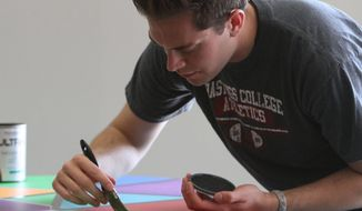 ADVANCE FOR SUNDAY, MAY 25 AND THEREAFTER - In a May 7, 2014 photo, Beau Neville fills in the lines on a piano he is painting in the Hazelrigg Student Union at Hastings College in Hastings, Neb. Using interior latex paint, he is covering it with red, blue, green, orange and purple triangles, rhombuses and other geometric shapes.  (AP Photo/Hastings Tribune, Amy Roh)