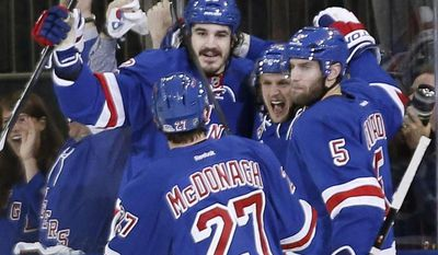 New York Rangers teammates celebrate with left wing Carl Hagelin, second from right, after Hagelin scored during the first period of Game 4 of the NHL hockey Stanley Cup playoffs Eastern Conference finals, Sunday, May 25, 2014, in New York. From left are defenseman Ryan McDonagh (27), center Brian Boyle (22), Hagelin and defenseman Dan Girardi (5). (AP Photo/Kathy Willens)