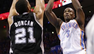Oklahoma City Thunder forward Serge Ibaka (9) shoots in front of San Antonio Spurs forward Tim Duncan (21) in the first quarter of Game 3 of an NBA basketball playoff series of the Western Conference finals, Sunday, May 25, 2014, in Oklahoma City. (AP Photo/Sue Ogrocki)