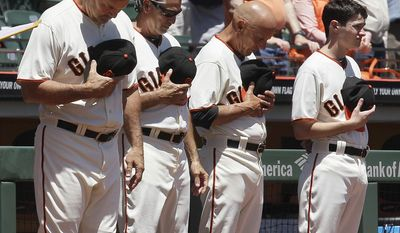 San Francisco Giants manager Bruce Bochy, from left, bench coach Ron Wotus, and third base coach Tim Flannery observe a moment of silence in honor of Memorial Day weekend before a baseball game against the Minnesota Twins in San Francisco, Sunday, May 25, 2014. (AP Photo/Jeff Chiu)
