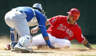 Kansas City Royals catcher Salvador Perez, left, tags out Los Angeles Angels' Albert Pujols (5) who was attempting to score from second base on a single hit by Angels' C.J. Cron for the last out of the seventh inning of a baseball game on Sunday, May 25, 2014, in Anaheim, Calif. (AP Photo/Alex Gallardo)