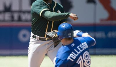 Oakland Athletics second baseman Alberto Callaspo, left, forces out Toronto Blue Jays' Steve Tolleson (18) then turns the double play over to first base to out Blue Jays catcher Erik Kratz during the fourth inning of a baseball game in Toronto on Sunday, May 25, 2014. (AP Photo/The Canadian Press, Nathan Denette)