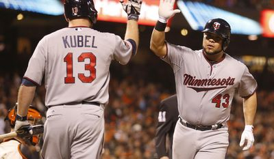 Minnesota Twins catcher Josmil Pinto (43) is congratulated by teammate Jason Kubel (13) after hitting a solo home run against the San Francisco Giants in the ninth inning of a baseball game Saturday, May 24, 2014, in San Francisco. (AP Photo/Tony Avelar)