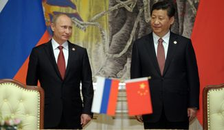 Russia's President Vladimir Putin and China's President Xi Jinping smile during a signing ceremony in Shanghai of a long-awaited, 30-year deal to buy Russian natural gas. (Associated Press)