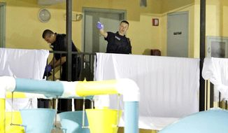 Myrtle Beach Police investigate where two bodies are behind the sheets on the walkway that's over a water park in front of the Bermuda Sands Resort late Saturday, May 24, 2014. Police report three people were killed and one was injured late Saturday. (AP Photo/The Sun News, Janet Blackmon Morgan)