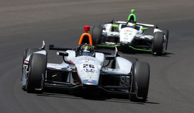 Kurt Busch (26) leads Sebastien Bourdais, of France, through the first turn during the 98th running of the Indianapolis 500 IndyCar auto race at the Indianapolis Motor Speedway in Indianapolis, Sunday, May 25, 2014. (AP Photo/Tom Strattman)