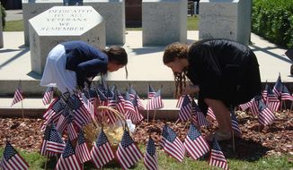 Jenna Watson, 9, of Stella, and MaKenna Yarbrough, 13, of Cape Carteret, helped place flags at the Carteret County Veterans Memorial following a Memorial Day ceremony Saturday, May 24, 2014, in Beaufort, N.C. (AP Photo/The Jacksonville Daily News, Jannette Pippin)