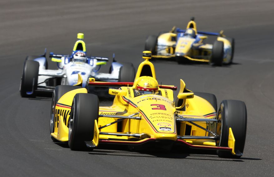Helio Castroneves, of Brazil, leads JR Hildebrand, center, and Marco Andretti through the first turn during the Indianapolis 500 IndyCar auto race at the Indianapolis Motor Speedway in Indianapolis, Sunday, May 25, 2014. (AP Photo/Tom Strattman)