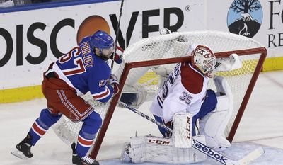 New York Rangers' Benoit Pouliot, left, pushes the net onto Montreal Canadiens goalie Dustin Tokarski during the second period of Game 4 of the NHL hockey Stanley Cup playoffs Eastern Conference finals, Sunday, May 25, 2014, in New York. (AP Photo/Seth Wenig)