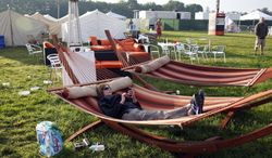 """Mary Milz, of Indianapolis, lies in a hammock, in the """"Glamping"""" area in the infield at the Indianapolis Motor Speedway before the start of Indianapolis 500 IndyCar auto race in Indianapolis, Sunday, May 25, 2014. The 98th running of the Indianapolis 500 was Sunday. (AP Photo/Tom Strattman)"""