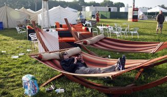 "Mary Milz, of Indianapolis, lies in a hammock, in the ""Glamping"" area in the infield at the Indianapolis Motor Speedway before the start of Indianapolis 500 IndyCar auto race in Indianapolis, Sunday, May 25, 2014. The 98th running of the Indianapolis 500 was Sunday. (AP Photo/Tom Strattman)"