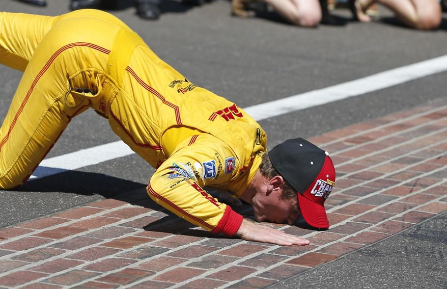 Ryan Hunter-Reay kisses the bricks after winning the 98th running of the Indianapolis 500 IndyCar auto race at the Indianapolis Motor Speedway in Indianapolis, Sunday, May 25, 2014. (AP Photo/Robert Baker)