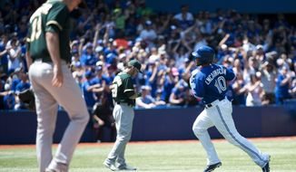 Toronto Blue Jays first baseman Edwin Encarnacion, right, rounds the bases past Oakland Athletics starting pitcher Drew Pomeranz, left, after hitting a solo home run during the fourth inning of a baseball game in Toronto on Sunday, May 25, 2014. (AP Photo/The Canadian Press, Nathan Denette)