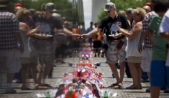 Terry Barlow, 66, of Thornton, Colo, a Marine Corps veteran who fought in Vietnam, touches a name on the Vietnam Veterans Memorial Sunday, May 25, 2014 during Memorial Day events in Washington. (AP Photo/Jacquelyn Martin)