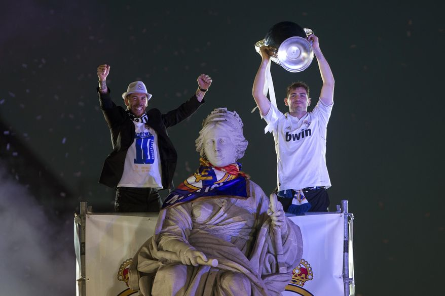Real Madrid's goalkeeper Iker Casillas, right, lifts the trophy with Sergio Ramos next to the Cibeles statue in Madrid, Spain, Sunday, May 25, 2014, after their team won the Champions League final soccer match in Lisbon, Portugal by beating Atletico Madrid. (AP Photo/Paul White)