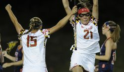 Maryland's Taylor Cummings (21) reacts after scoring with Zoe Stukenberg (15) against Syracuse in the first half of an NCAA championship lacrosse game Sunday, May 25, 2014, in Baltimore.(AP Photo/Gail Burton)
