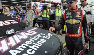 Kurt Busch walks to his car before the start of the NASCAR Sprint Cup series Coca-Cola 600 auto race at Charlotte Motor Speedway in Concord, N.C., Sunday, May 25, 2014. Busch finished sixth in the Indianapolis 500 earlier. (AP Photo/Mike McCarn)