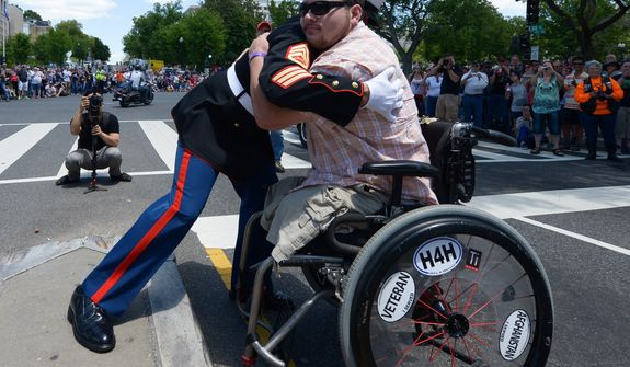 Double amputee United States Marine Corp Cpl. Sean Adams, of Gainesville, GA, embrace after Adams saluted Chambers, during the 25th anniversary of the Rolling Thunder Ride for Freedom at the base of the Memorial Bridge on Sunday, May 25. Khalid Naji-Allah/ Special for the Washington Times