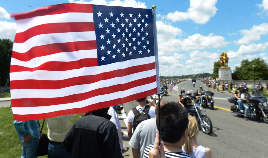 An unidentified person waves the U.S. Flag during the Rolling Thunder in the 25th anniversary of the Rolling Thunder Ride for Freedom at the base of the Memorial Bridge on Sunday, May 25. Khalid Naji-Allah/ Special for the Washington Times