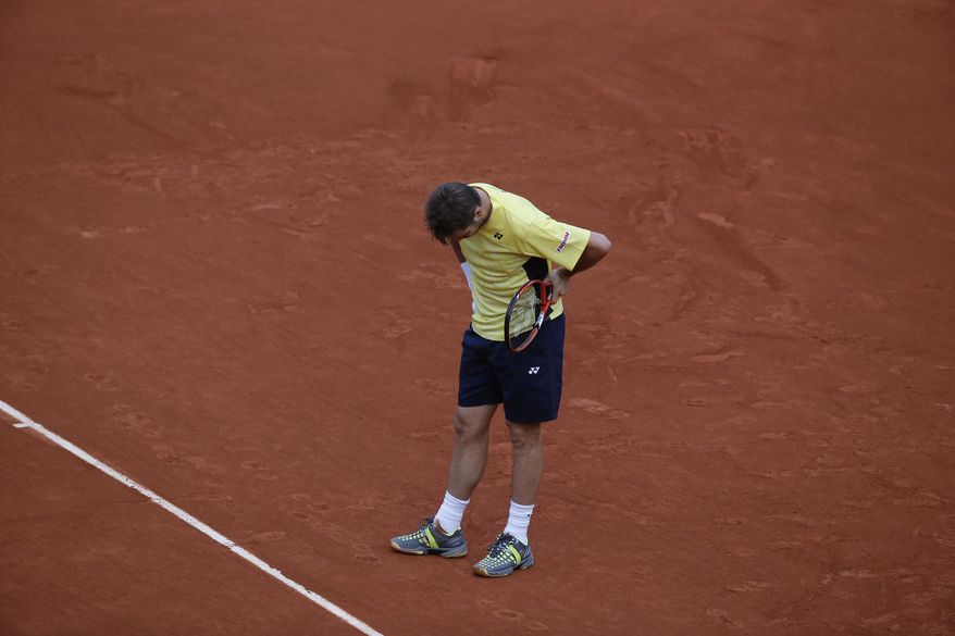 Switzerland's Stanislas Wawrinka bows his head after missing a return during the first round match of the French Open tennis tournament against Spain's Guillermo Garcia-Lopez at the Roland Garros stadium, in Paris, France, Monday, May 26, 2014. Wawrinka lost in four sets. (AP Photo/Michel Euler)
