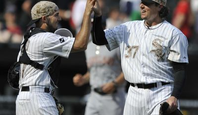 Chicago White Sox closing pitcher Scott Downs (37), celebrates with catcher Adrian Nieto left, after defeating the Cleveland Indians 6-2 during a baseball game in Chicago, Monday, May 26, 2014. (AP Photo/Paul Beaty)