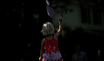 Emilia Thorsson, 2, waves an American flag as she sits on top of her father Thor's shoulders during the Glacier Highlands Memorial Day parade in the Glacier Highlands neighborhood in Ann Arbor, Mich., Monday, May 26, 2014. (AP Photo/The Ann Arbor News, Melanie Maxwell)