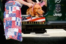 Retired Army Military Intelligence Officer Angelee Andoe of Lorton, Va., sits with her service dog, Franklin Delano Roosevelt, a golden retriever as they get ready to march with a group of Hero Dogs in the National Memorial Day Parade along Constitution Ave., Washington, D.C., Monday, May 26, 2014. Andoe, who suffers from PTSD, is helped by F.D.R. who is given to her by Hero Dogs, a non-profit which helps provide improved quality of life to Veterans with disabilities by raising, training, and placing service dogs with Veterans who have served honorably in the United States Armed Services. (Andrew Harnik/The Washington Times)