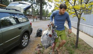 Mike Willyaung moves his belongings back in Kachina Village, Monday, May 26, 2014, near Flagstaff  Ariz.  Willyaung headed pre-evacuation orders due to the Slide Fire. Crews have mostly completed burnout operations on the key northern flank of the Slide Fire and are preparing to make similar protection efforts on the fire's western end. (AP Photo/The Arizona Republic, David Kadlubowski)  MARICOPA COUNTY OUT; MAGS OUT; NO SALES