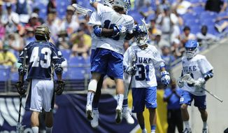 Duke's Myles Jones, center rear, and Deemer Class, center foreground, celebrate a goal against Notre Dame in the first half of an NCAA college men's championship lacrosse game Monday, May 26, 2014, in Baltimore.(AP Photo/Gail Burton)