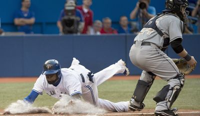 Toronto Blue Jays Jose Reyes, left, slides safe at home plate past Tampa Bay Rays catcher Ryan Hanigan, right, during the first inning of a baseball game in Toronto on Monday, May 26, 2014. (AP Photo/The Canadian Press, Nathan Denette)