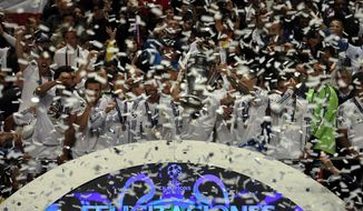 Real Madrid players are covered in confetti as they hold the Champion League trophy at the end of the Champions League final soccer match between Atletico de Madrid and Real Madrid in Lisbon, Portugal, Saturday, May 24, 2014. (AP Photo/Daniel Ochoa de Olza)