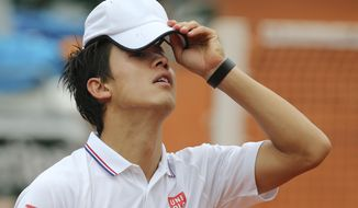 Japan's Kei Nishikori adjusts his cap in the first round match of the French Open tennis tournament against Slovakia's Martin Klizan at the Roland Garros stadium, in Paris, France, Monday, May 26, 2014. Nishikori lost in three sets 6-7, 1-6, 2-6. (AP Photo/David Vincent)