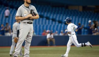 Tampa Bay Rays starting pitcher Erik Bedard looks on as Toronto Blue Jays Steve Tolleson, right, rounds the bases after hitting a solo home run during fourth inning of a baseball game in Toronto on Monday, May 26, 2014. (AP Photo/The Canadian Press, Nathan Denette)