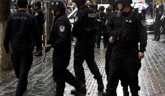 Policemen prepare to patrol Urumqi, a city northwest China's Xinjiang Uygur Autonomous Region, after an explosion on May 22, 2014. (Associated Press) ** FILE **