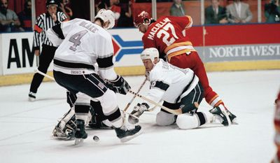 **FILE** Los Angeles Kings Larry Robinson (19) and Rob Blake (4) along with Calgary Flames Brian MacLellan (27) scramble for the puck during early NHL playoff action April 14, 1990 in Inglewood, Calif. (AP Photo)