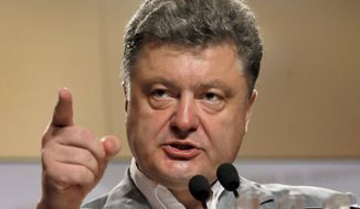 Ukrainian presidential candidate Petro Poroshenko gestures, during a press conference, in Kiev, Ukraine, Monday, May 26, 2014.  The leader of the Ukrainian presidential race, Pyotr Poroshenko, does not intend to stop the use of force in the southeast of the country. He made this statement at a news conference on Monday. (AP Photo/Efrem Lukatsky)