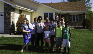 In this May 22, 2014 photo, after a tornado completely demolished their home in Beaver Crossing on May 11, the Nisly family poses for a photo together in front of their new home in Utica, Neb. Since the tornado, the family had been living in a three-bedroom house owned by the Utica United Methodist Church, and sleeping on air mattresses. (AP Photo/The Journal-Star, Dan Little) LOCAL TV OUT; KOLN-TV OUT; KGIN-TV OUT; KLKN-TV OUT