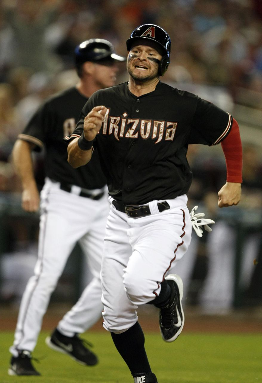Arizona Diamondbacks left fielder Cody Ross scores after a misplayed ball by San Diego Padres third baseman Chase Headley in the first inning of a baseball game, Monday, May 26, 2014, in Phoenix. (AP Photo/Rick Scuteri)