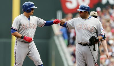 Texas Rangers' Shin-Soo Choo, left, of Korea, is congratulated by first base coach Bengie Molina after his single off Minnesota Twins pitcher Kevin Correia in the fifth inning on a baseball game Monday, May 26, 2014, in Minneapolis. (AP Photo/Jim Mone)