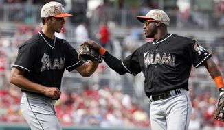 Miami Marlins relief pitcher Steve Cishek, left, celebrates with shortstop Adeiny Hechavarria after a baseball game against the Washington Nationals at Nationals Park Monday, May 26, 2014, in Washington. The Marlins won 3-2. (AP Photo/Alex Brandon)